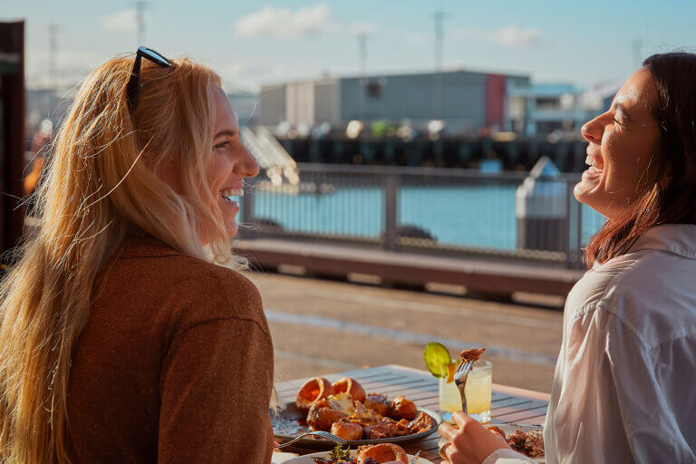 Two laughing ladies on waterfront - mini break campaign