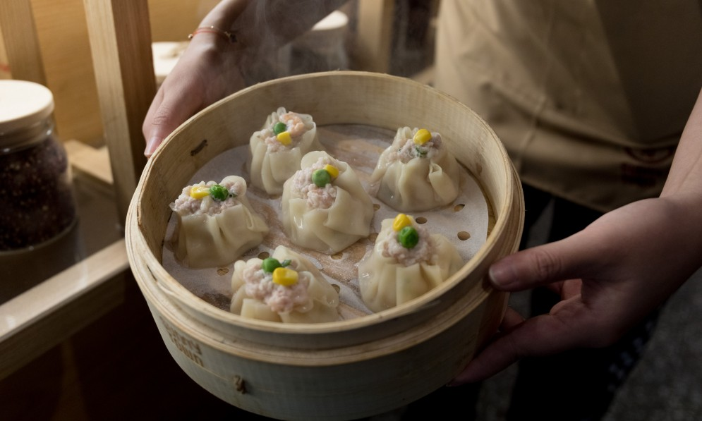 Man holding tray of dumplings
