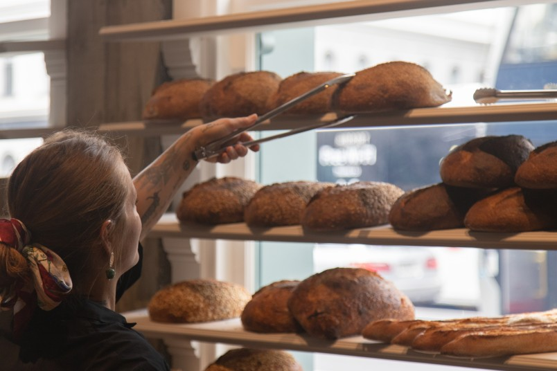 A worker selecting a loaf from shelves of bread at Daily Bread, Britomart.