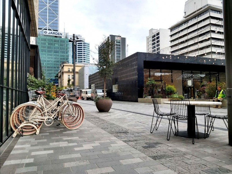 Galway Street in Britomart - an attractively paved shared space with bikes parked in front of a building and outdoor cafe seating.