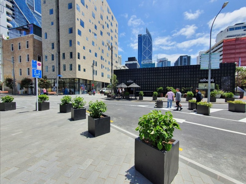 Planters in the foreground, the Hotel Britomart and blue sky in the background, with Britomart's newly upgraded Gore Street in the middle.